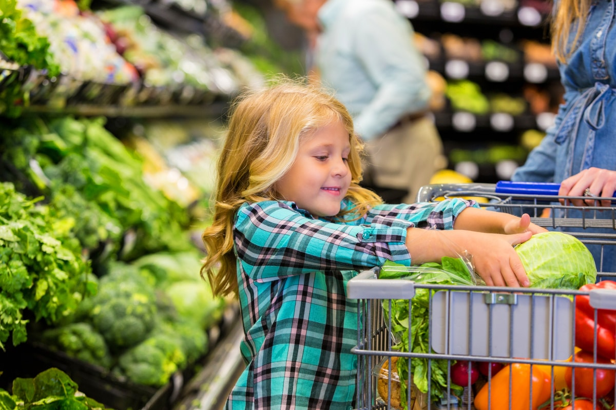Young healthy child shopping for organic produce